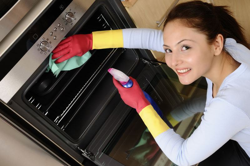 a lady cleaning an oven